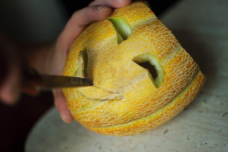 Melón inusual de Halloween, cortando las manos del proceso, del cuchillo y del varón imagen de archivo libre de regalías