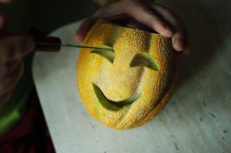 Melón inusual de Halloween, cortando las manos del proceso, del cuchillo y del varón imagenes de archivo