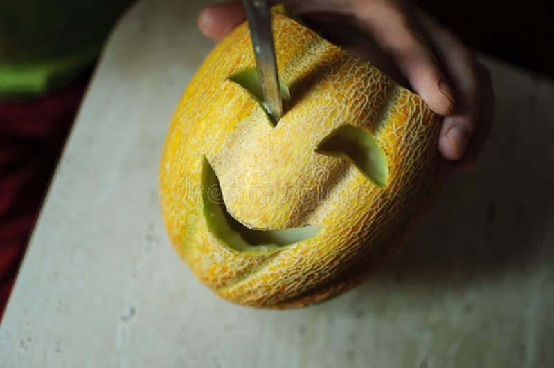 Melón inusual de Halloween, cortando las manos del proceso, del cuchillo y del varón imágenes de archivo libres de regalías