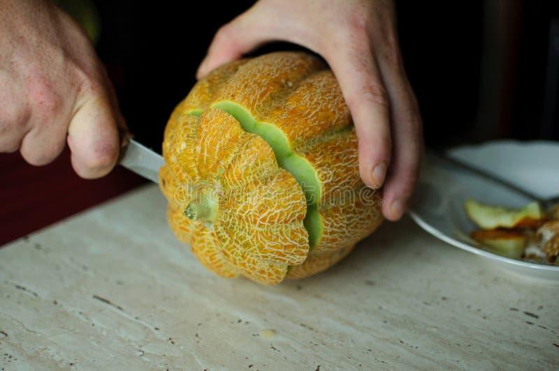 Melón inusual de Halloween, cortando proceso, las semillas y las sobras en la tabla de cocina fotografía de archivo