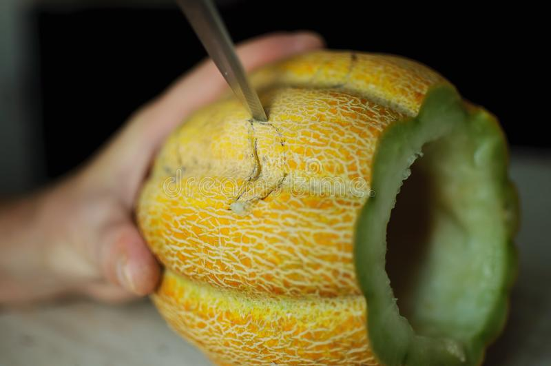 Melón inusual de Halloween, cortando proceso, las semillas y las sobras en la tabla de cocina, el cuchillo y las manos del varón fotografía de archivo libre de regalías