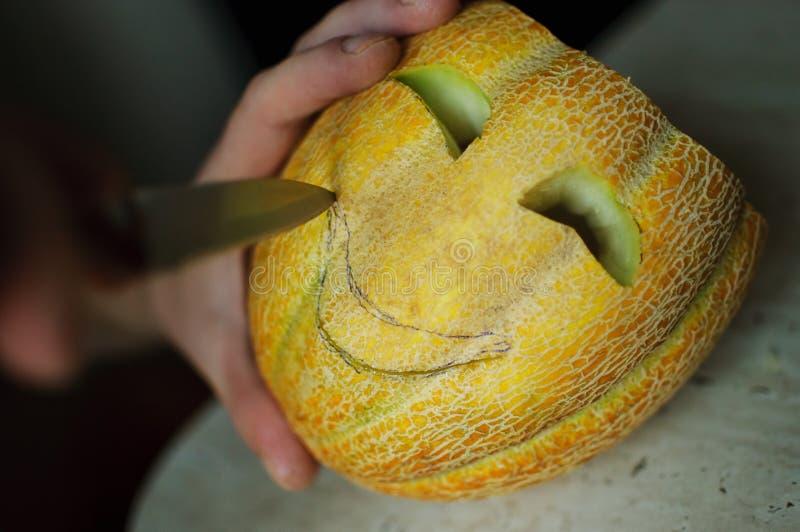 Melón inusual de Halloween, cortando proceso, las semillas y las sobras en la tabla de cocina, el cuchillo y las manos del varón foto de archivo