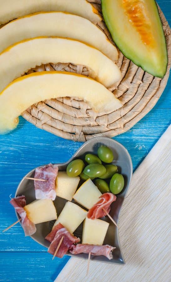 Melón, jamón y aceitunas italianos sabrosos del cantalupo del aperitivo fotografía de archivo