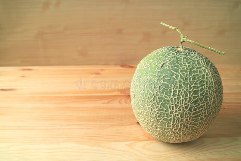 Melón maduro fresco del cantalupo o fruta entera del melón con el tronco aislado en la tabla de madera fotografía de archivo
