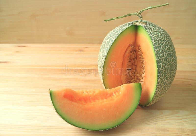 Melón maduro jugoso del cantalupo del color anaranjado brillante cortado de la fruta entera aislada en la tabla de madera fotografía de archivo