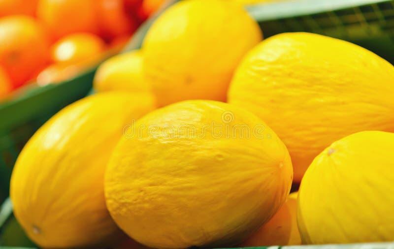 Melões amarelos frescos indicados em um greengrocery imagens de stock royalty free