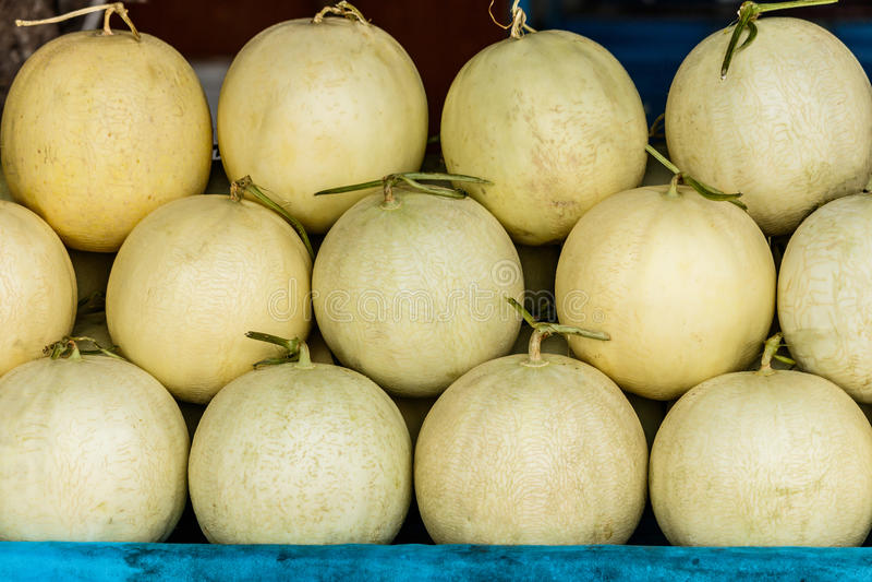 Melões orgânicos frescos do cantalupo empilhados na tabela para a venda no lugar foto de stock