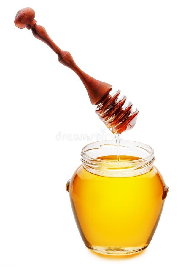 Mel dourado em um frasco com um mel de derramamento do dripper de madeira do mel imagens de stock royalty free