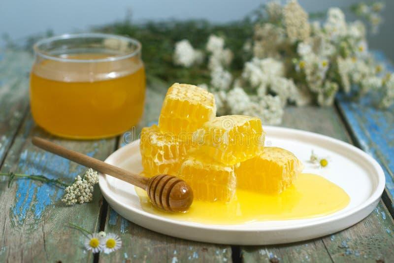 Mel em um frasco de vidro e mel nos favos de mel imagem de stock royalty free