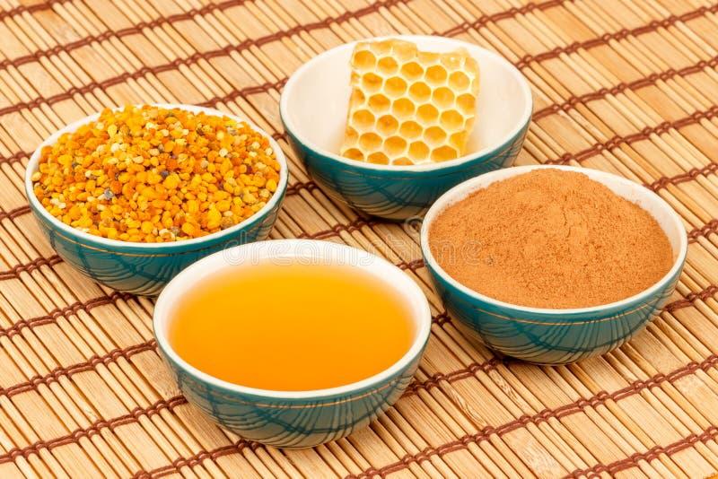 Mel, favo de mel, pólen e canela em umas bacias fotos de stock