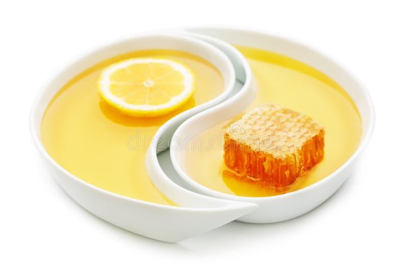 Mel, um favo de mel e uma fatia do limão em duas bandejas de yang do yin, i fotografia de stock royalty free