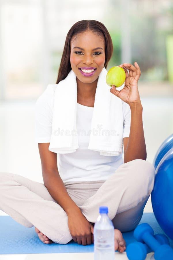 Mela afroamericana della tenuta della donna fotografia stock