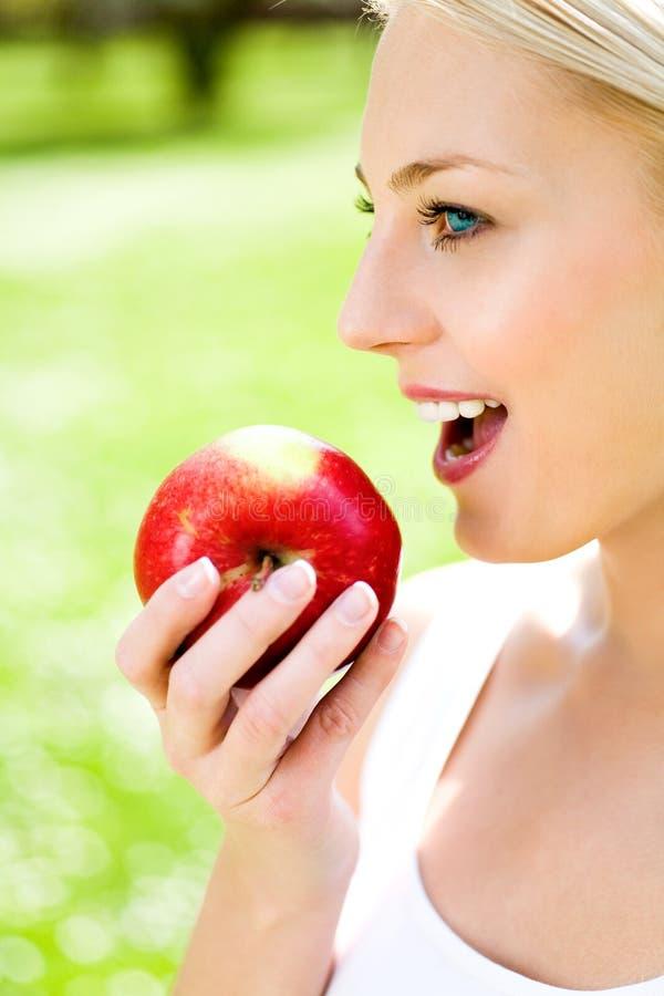 mela che mangia donna rossa fotografie stock