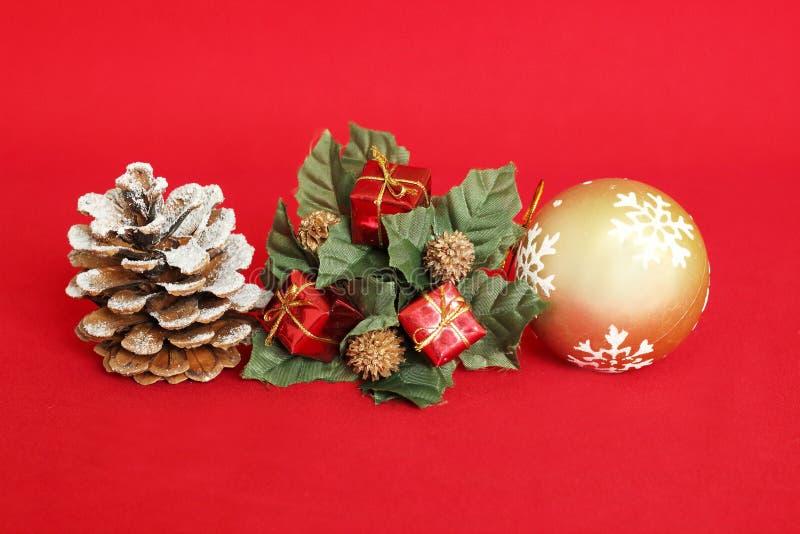 mela del pino con neve, i regali rossi e una palla dorata su un fondo rosso per la decorazione di festa fotografia stock libera da diritti