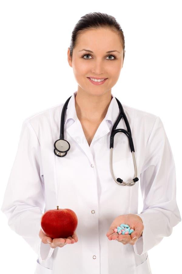 Mela e pillole della holding del medico immagine stock libera da diritti
