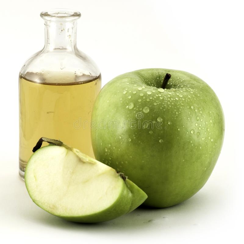 Mela ed aceto verdi della mela in bottiglia di vetro su bianco fotografie stock
