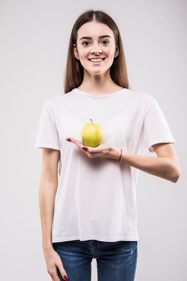 Mela felice della tenuta della donna su un fondo bianco esaminando macchina fotografica Concetto di salute immagini stock