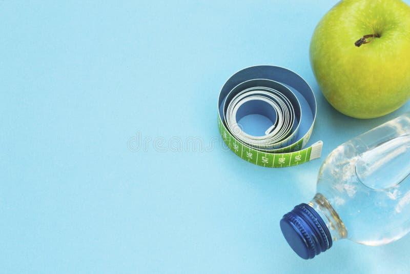 Mela fresca, nastro di misurazione e bottiglia di acqua su fondo blu fotografia stock