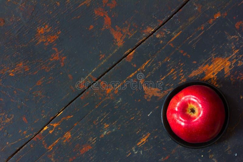 Mela matura rossa in un piattino nero su vecchio fondo immagini stock libere da diritti