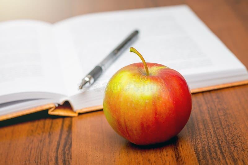 Mela matura rossa vicino al libro aperto Mangiando in una rottura fra occupat immagine stock libera da diritti