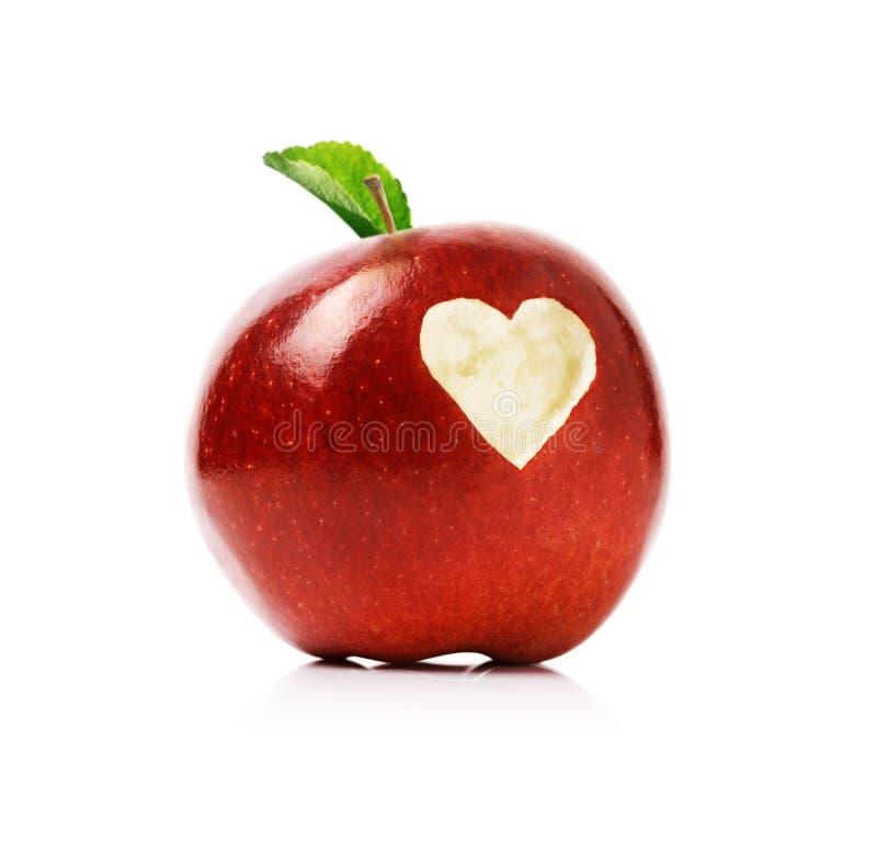 Mela rossa con il simbolo del cuore fotografie stock