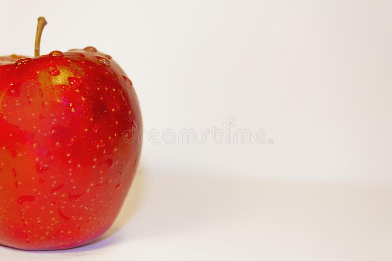 Mela rossa con le gocce dell'acqua immagini stock