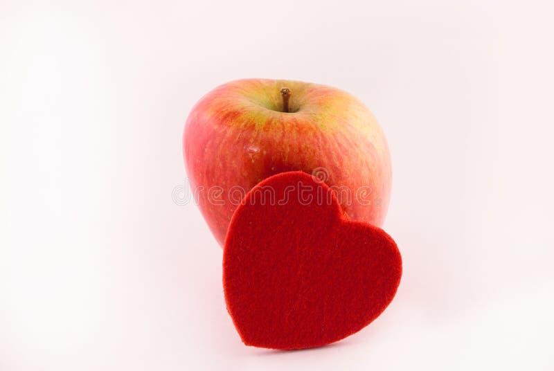 Mela rossa ed il cuore fotografia stock