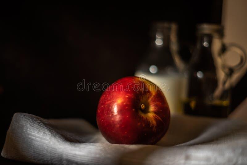 Mela rossa fresca su tessuto di tela con il fondo vago delle bottiglie di vetro immagini stock libere da diritti