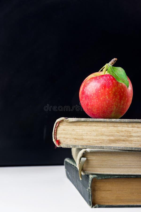 Mela rossa viva con il gambo e foglia verde sopra la pila di vecchi libri sullo scrittorio bianco in aula Lavagna Di nuovo al ban immagine stock libera da diritti
