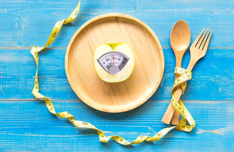 Mela verde con la bilancia e nastro di misurazione per il dimagramento di dieta sana fotografia stock