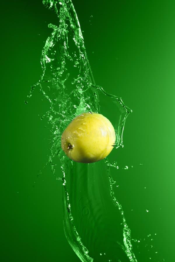 Mela verde con la spruzzata dell'acqua, su verde fotografia stock