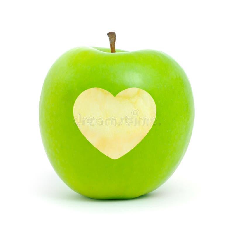 Mela verde con un simbolo del cuore fotografie stock