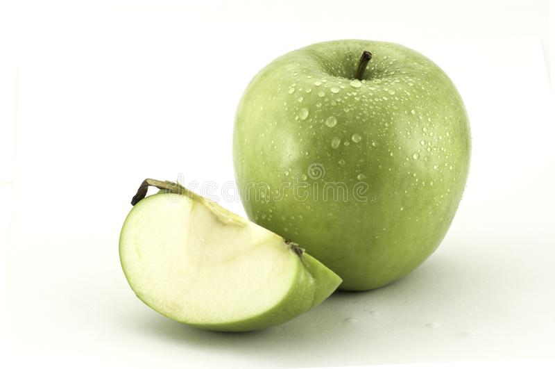 Mela verde e una fetta di mela su fondo bianco fotografia stock libera da diritti