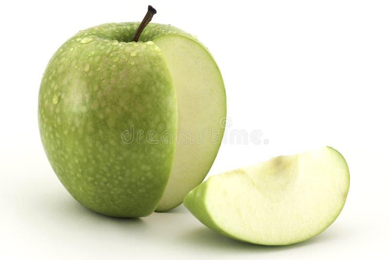 Mela verde ed una fetta su fondo bianco fotografia stock libera da diritti