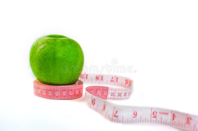 Mela verde fresca e nastro di misurazione isolati su fondo bianco immagini stock