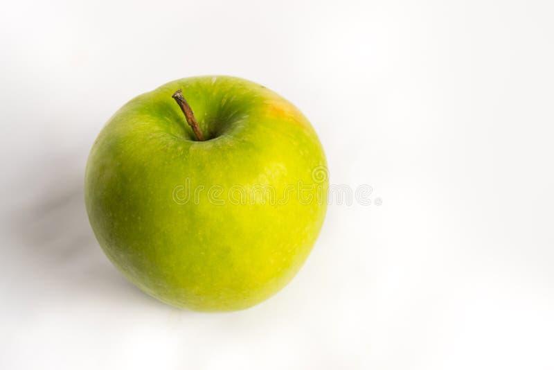 Mela verde su un fondo bianco isolato immagini stock
