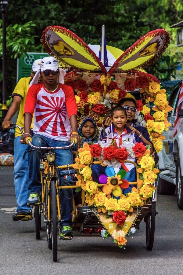 MELAKA, MALEISIË - AUGUSTUS 22: Trishawruiter met een verfraaide kleurrijke pedicab royalty-vrije stock fotografie