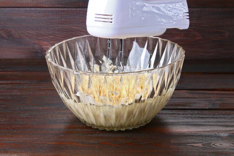Melanżer w ręki porywającym cieście dla muffins na drewnianym stole obraz stock