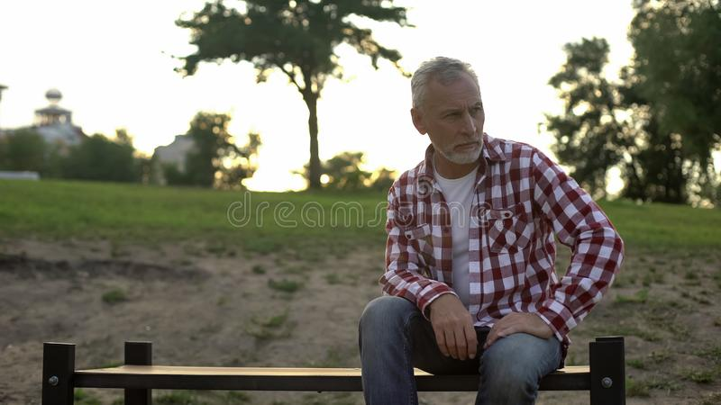 Melancholic elderly male sitting on bench in park and thinking about problems stock photos