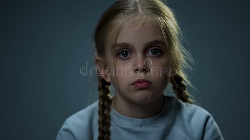 Melancholic girl looking at camera, piercing glance, child hoping for happiness royalty free stock photo