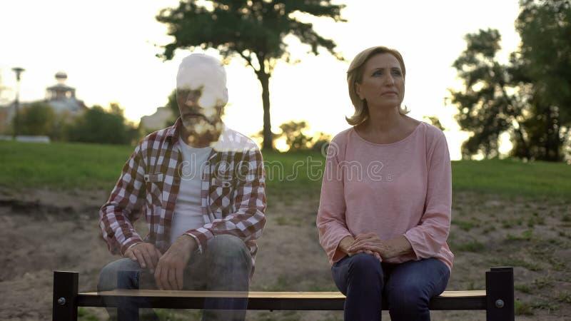 Melancholic mature woman sitting on bench, thinking about husband, beloved loss stock photography