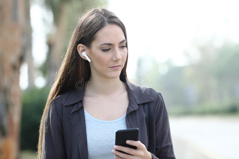 Melancholic woman listening to music in a park royalty free stock photo