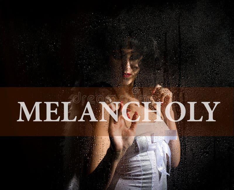 Melancholie op het virtuele scherm wordt geschreven dat Hand van jonge vrouw melancholisch en droevig bij het venster in de regen stock afbeeldingen