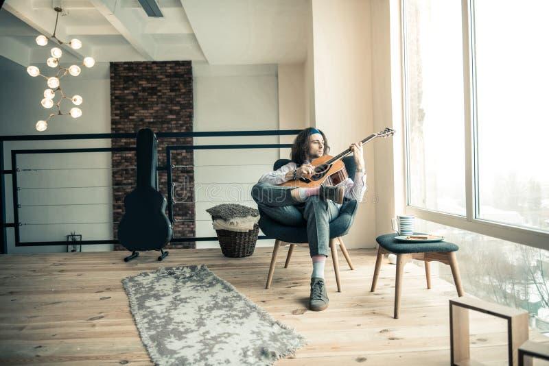 Melancholijny elegancki muzyk jest samotny i siedzi w jaskrawym pokoju w domu fotografia royalty free