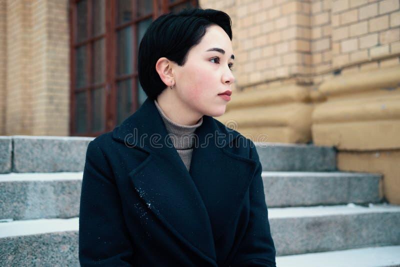 Melancholijny portret młoda azjatykcia kobieta z krótkim włosianego stylu obsiadaniem na schody obraz royalty free