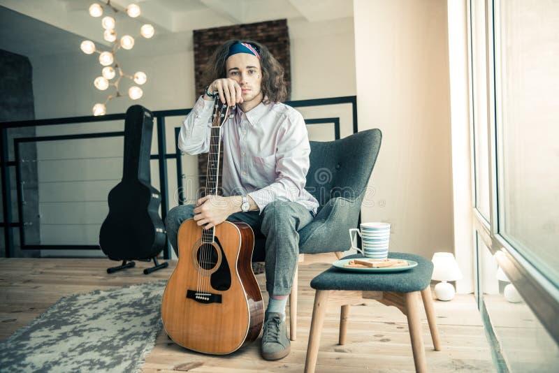 Melancholijny przystojny muzyk pokazuje gitarę akustyczną podczas gdy trzymający je zdjęcie royalty free
