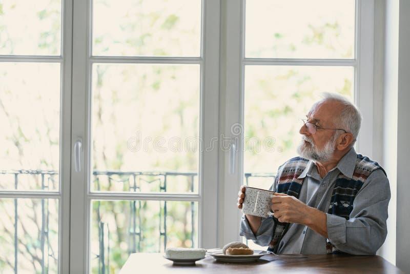 Melancholische grootvader die ontbijt eten al alleen bij de lijst stock afbeelding