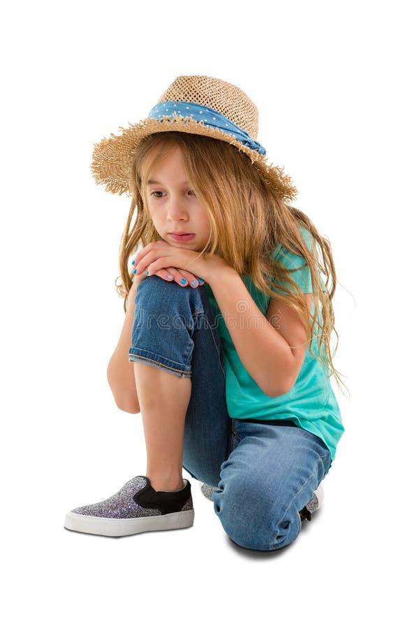 Melancholisches Mädchenknienanstarren entlang des Bodens lizenzfreies stockbild