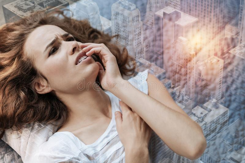 Melancholy girl lying against urban background. Being alone. Attractive woman wrinkling forehead and opening mouth while having some problems royalty free stock images
