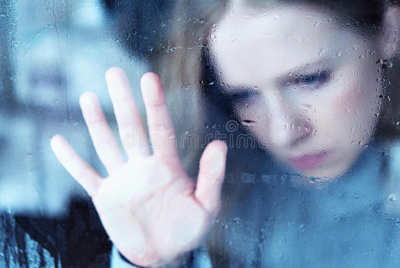 Melancholy and sad girl at the window in the rain royalty free stock photo